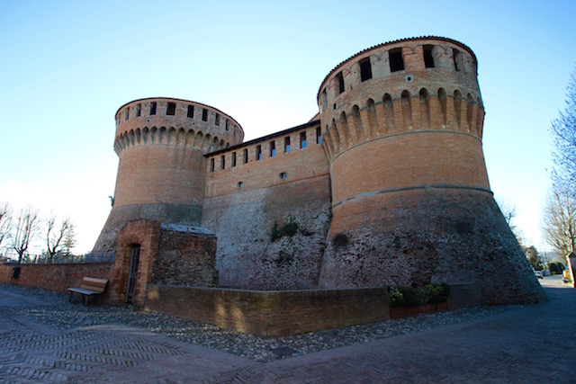 на фото крепость La Rocca в городе Доцца, Италия
