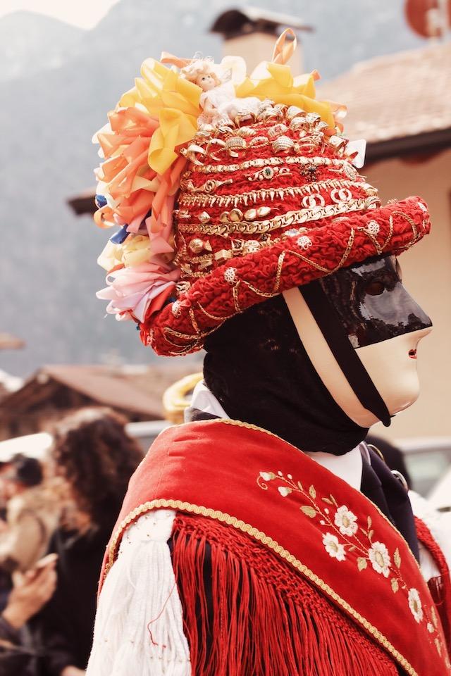 на фото богато украшенная драгоценностями шляпа - часть карнавального костюма танцора в городе Баголино в Италии